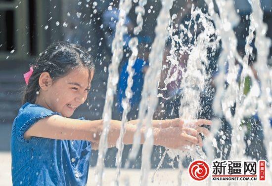 13日,在黄河路,9岁的帕孜拉・阿布都克尤木在喷泉旁玩耍。(本报全媒体记者张利民摄)
