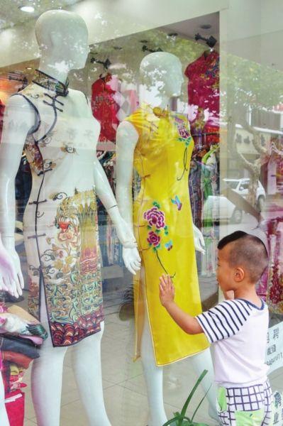十全街一家旗袍店门前,小男孩好奇地望着橱窗里的模特。吕明