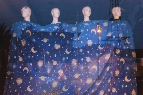 """天色渐暗,""""工作""""了一天的模特也累了,裹着印有星星月亮的布帘准备入眠。 钱前 摄"""