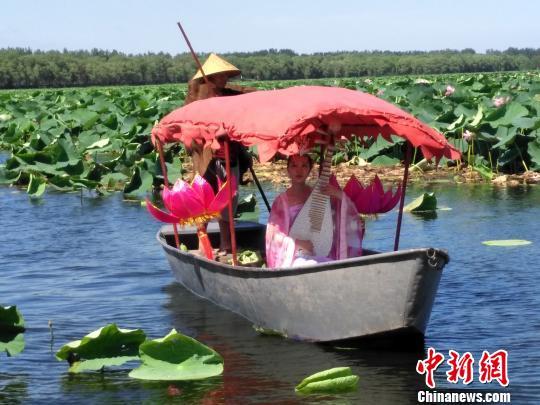 """""""荷花仙子""""坐在船上演奏美妙的琵琶。 赵桂华 摄"""