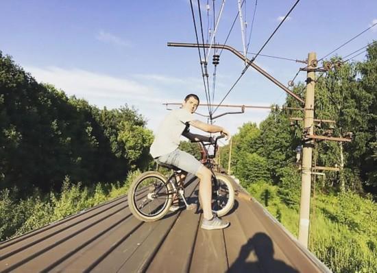 玩命!俄两小伙火车顶上骑单车 险出意外遭众责