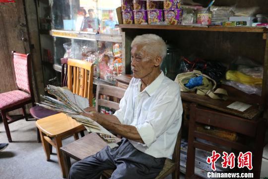 """图为韦宣周在展示其珍藏的""""家书""""。 林馨 摄"""