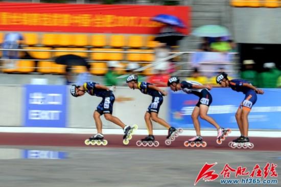 四位比赛选手从主看台前滑过