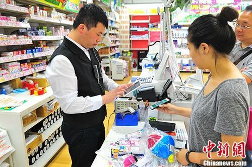 """资料图:7月3日,在东京著名繁华街区涩谷的一家商店内,顾客尝试用来自中国企业的""""扫码支付""""付款。 <a target='_blank'  data-cke-saved-href='http://www.chinanews.com/' href='http://www.chinanews.com/' _fcksavedurl='http://www.chinanews.com/'></table><p  align="""