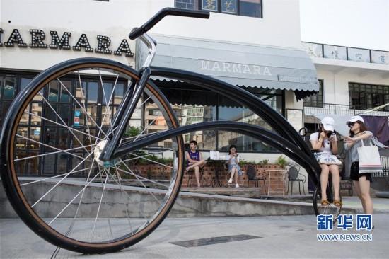 8月4日,在厦门市沙坡尾,游客在自行车雕塑前合影.