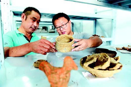 湖北日报讯 图为专家们在查看出土文物。