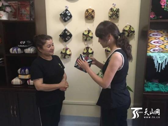 顾客在早热木·依明(左)的手工制作室购买小花帽.