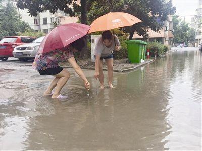 南通海门突降暴雨 社区干部冒雨疏通排水管道