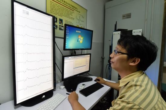 工作人员观看脑电波分析图。人民网记者 翁奇羽摄