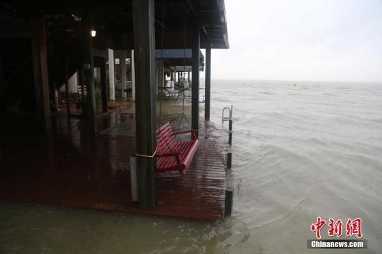 """大西洋飓风""""哈维""""于8月25日夜间登陆得州南部沿海地区后,26日上午,风速已降至1级。图为休斯敦东南方向60公里的kiki岛沿海居民楼。26日上午,海水恢复平静无大浪,海平面上涨正浸入居民楼平台。<a target='_blank'  data-cke-saved-href='http://www.chinanews.com/' href='http://www.chinanews.com/'><p  align="""