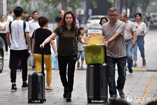 家长为孩子运送行李。(人民网记者 翁奇羽 摄)