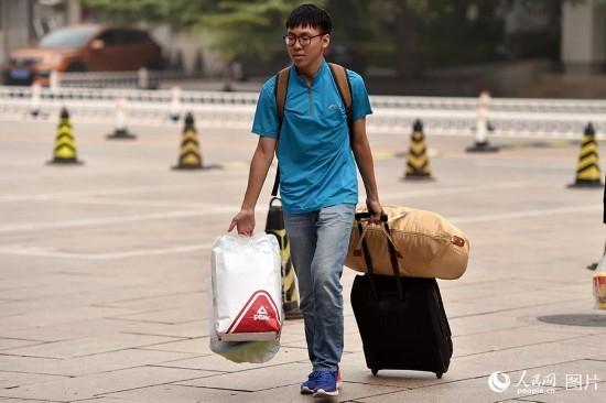 新生手提行李入学报到。(人民网记者 翁奇羽 摄)