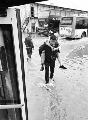 """暴雨淹了车场昆明公交员工背老两口""""过河"""""""