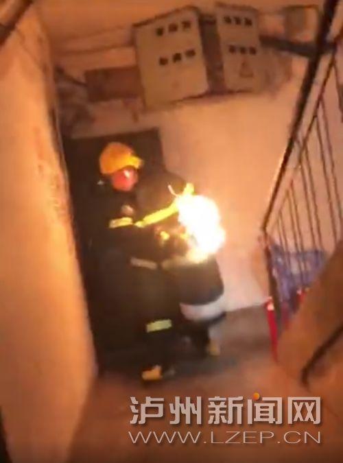 消防戰士抱著燃燒的氣罐沖出樓道 (視頻截圖)