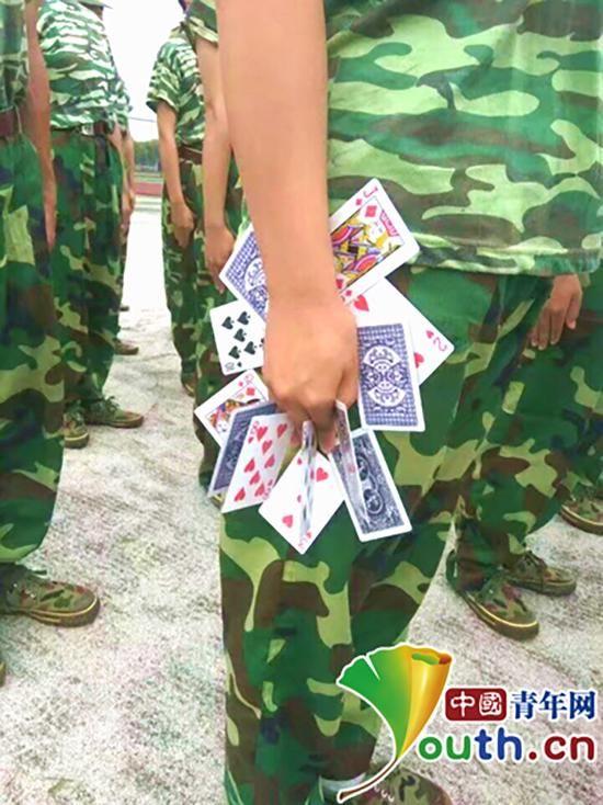 新生军训手夹10多张扑克牌站军姿 教官称是传统