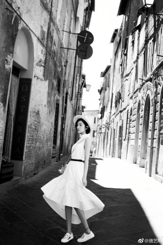 黑白复古风写真,照片中唐艺昕穿毛衣搭配长裙,戴著帽子,在街道上奔跑