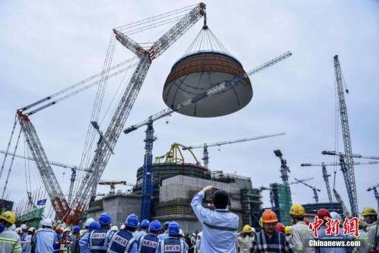 """资料图:5月25日下午5时58分,中国自主三代核电""""华龙一号""""全球首堆示范工程――中核集团福清核电5号机组穹顶吊装成功。<a target='_blank'  data-cke-saved-href='http://www.chinanews.com/' href='http://www.chinanews.com/'>中新社</a>发 钟鹰 摄"""