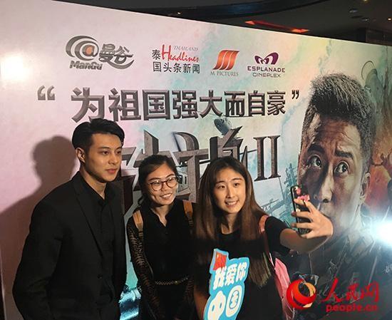 10月11日,泰国曼谷观众在《战狼2》泰国首映礼海报展板前合影。 俞懿春摄