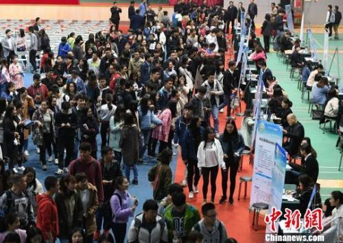 资料图:众多大学生扎堆招聘现场求职。杨华峰摄