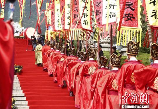 """写有""""国泰民安""""、""""敬天祈福""""的红色、黄色旌旗环绕泰山脚下。 陈阳 摄"""