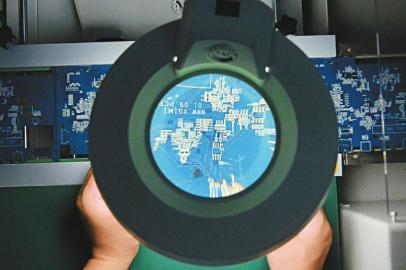 遂宁一家电子科技公司生产车间,工作人员通过放大镜检查电路板.