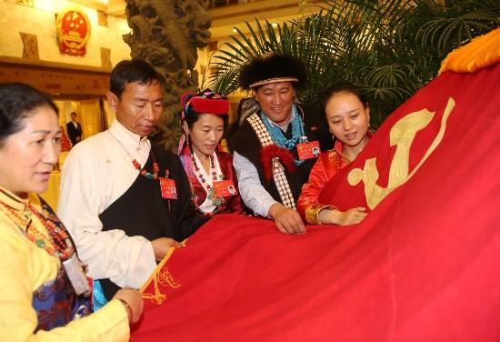 图为10月19日会议间隙,我区十九大代表在北京驻地共同展示这面党旗.
