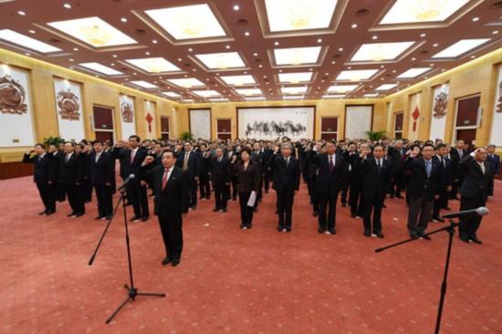 党的十九大代表及局级以上党员领导干部在机关会议厅,面对鲜艳的党旗