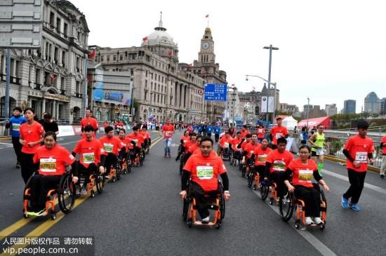 11月12日,2017上海国际马拉松赛在上海外滩金牛广场开跑,来自全球的38000名选手参赛。其中残疾人选手坐在轮椅上参赛。严大明/人民图片