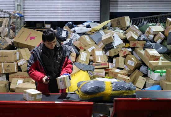11月12日清晨,在山东省潍坊市一家快递公司分拣中心,工作人员在分拣货件。 新华社发(张驰 摄)