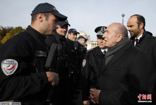 法国内长科隆(右2)近日与总理菲利普(右1)一同看望巴黎埃菲尔铁塔下执勤的警务人员。