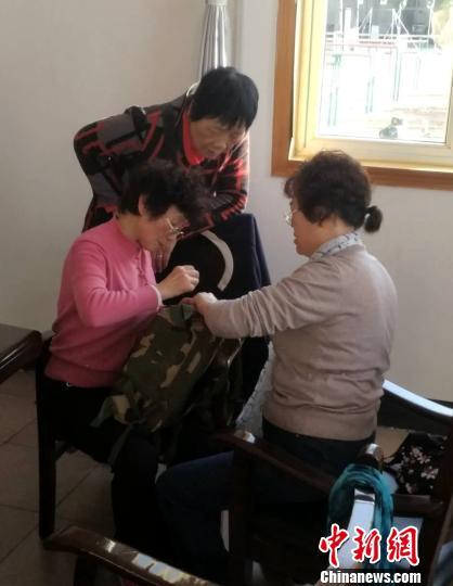 """图为""""老妈妈服务队""""的大妈们在为战士修补一个背包。 余攀峰 摄"""