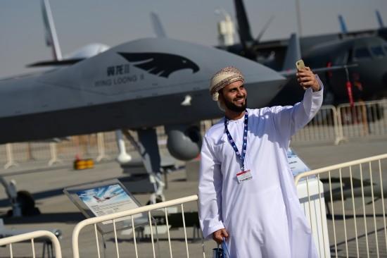 """11月13日,在阿联酋迪拜航展上,一名参观者在""""翼龙""""无人机全尺寸模型前自拍。"""