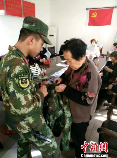 """图为一名战士将要修补的衣服拿给""""老妈妈服务队""""队修补。 宋留洋 摄"""