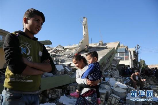 11月14日,在伊拉克苏莱曼尼亚省达尔班迪汗镇,当地民众聚集在地震废墟旁。