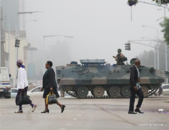 People walk past an armored vehicle on a street in Harare, capital of Zimbabwe, Nov. 15, 2017. Armored carriers cordoned off Zimbabwe's Presidential seat of power and Parliament Building in the capital while helicopters circled the city center on a drizzly morning, after the military announced it had taken over control of all government institutions. [Photo: Xinhua/Philimon Bulawayo]