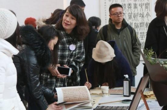 志愿者引导观众体验书法