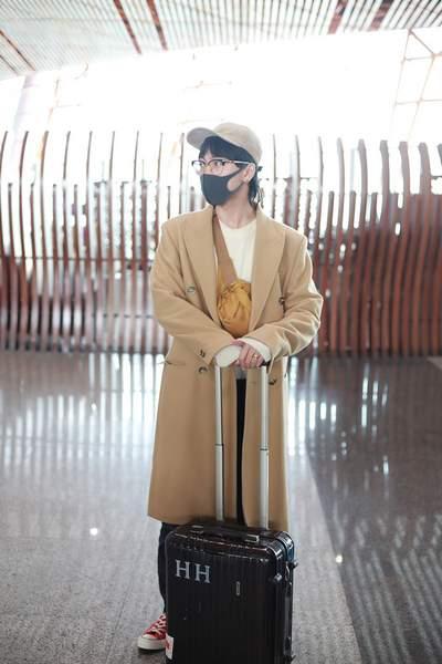 韩火火素颜出发上海维密 驼色大衣棒球帽秀慵懒男友穿搭