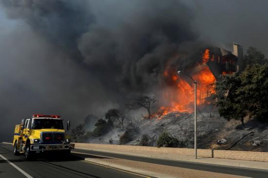 12月5日,在美国加利福尼亚州南部文图拉县,消防车经过一处着火建筑。新华社/路透
