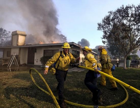 12月6日,消防员在美国洛杉矶贝莱尔住宅区火灾现场工作。