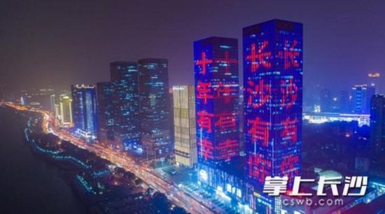 """今晚6时,湘江中路万达广场,楼宇亮化灯带逐一点亮,""""十年有幸,长沙有你""""字样在流动夜景中格外醒目。 长沙晚报记者 余劭�� 摄"""