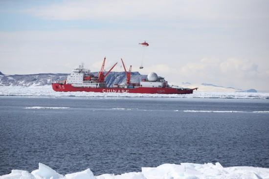 """12月9日,船载""""雪鹰12""""Ka-32直升机从""""雪龙""""号起飞,向恩克斯堡岛新建站区进行物资吊运作业。"""