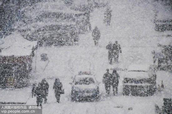 12月11日,行人在山东省烟台市福山区永安街冒雪出行。