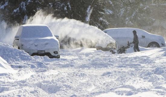 12月25日,在加拿大多伦多,一名男子帮助一辆在雪地中打滑的汽车脱困。