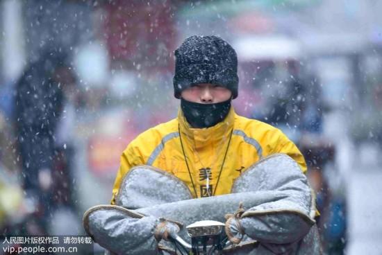 1月3日,受冷空气影响,安徽省亳州市迎来新年第一场降雪,人们在安徽省亳州市区街头冒雪出行。刘勤利/人民图片