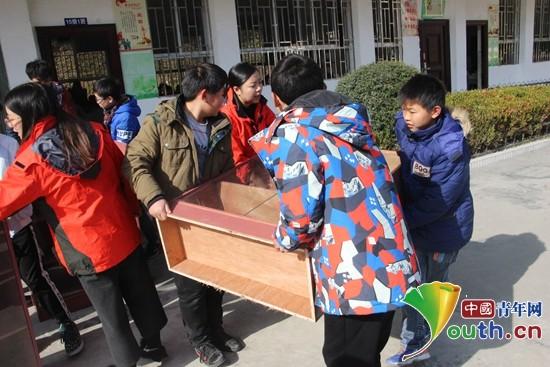 图为广西师大研支团志愿者与车田民族初中学生搬运书柜。广西师大研支团 供图
