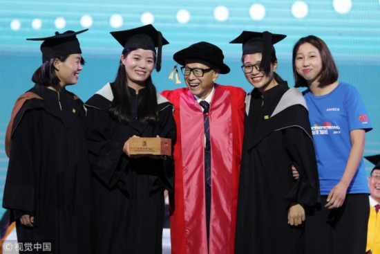Hong Kong business magnate Li Ka Shing (center) takes a group photo with the four members of Kung Fu Cha Cha during a graduation ceremony at Shantou University on June 27, 2017. [Photo: VCG]