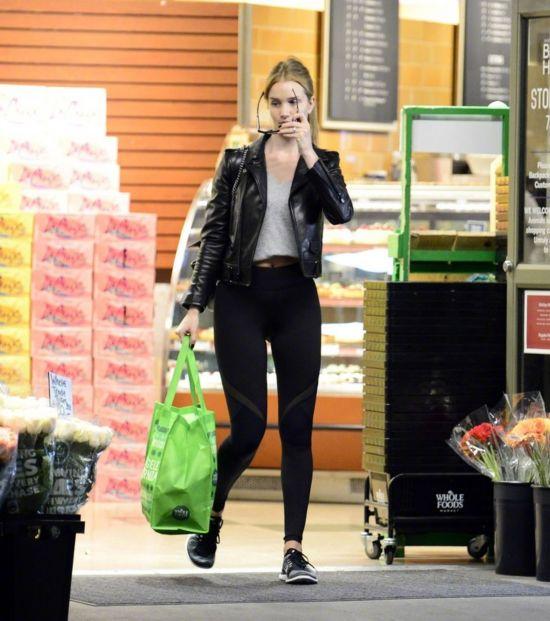 Rosie Huntington-Whiteley 当地时间2017年12月31日在洛杉矶 Whole Foods 购物的街拍。身穿的是Saint Laurent 黑色皮衣,配戴的是Cubitts 墨镜,脚穿Nike