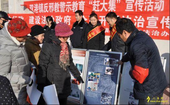 津南区双港镇工作人员组织群众观看反邪教展板