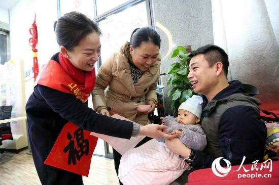 四个多月大的宝宝周墨(右二)随父母在上海虹桥火车站的母婴休息室内休息。上海虹桥心尚雷锋服务站的客运员邵玮(左一)耐心询问周墨一家是否需要帮忙,并向他们赠送了福字,传递了新春的祝福。