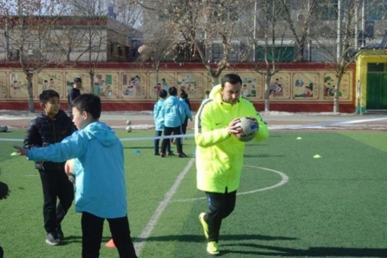 One of the coaches from Football Club Internazionale Milano teaches soccer at Xiongxian No 1 Primary School in North China's Hebei province, Jan 29, 2018. (Photo provided to chinadaily.com.cn)